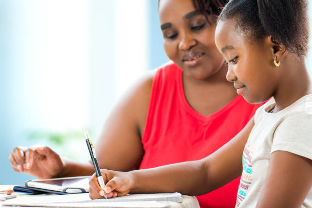 Little african girl doing home work with supervisor. stock photo