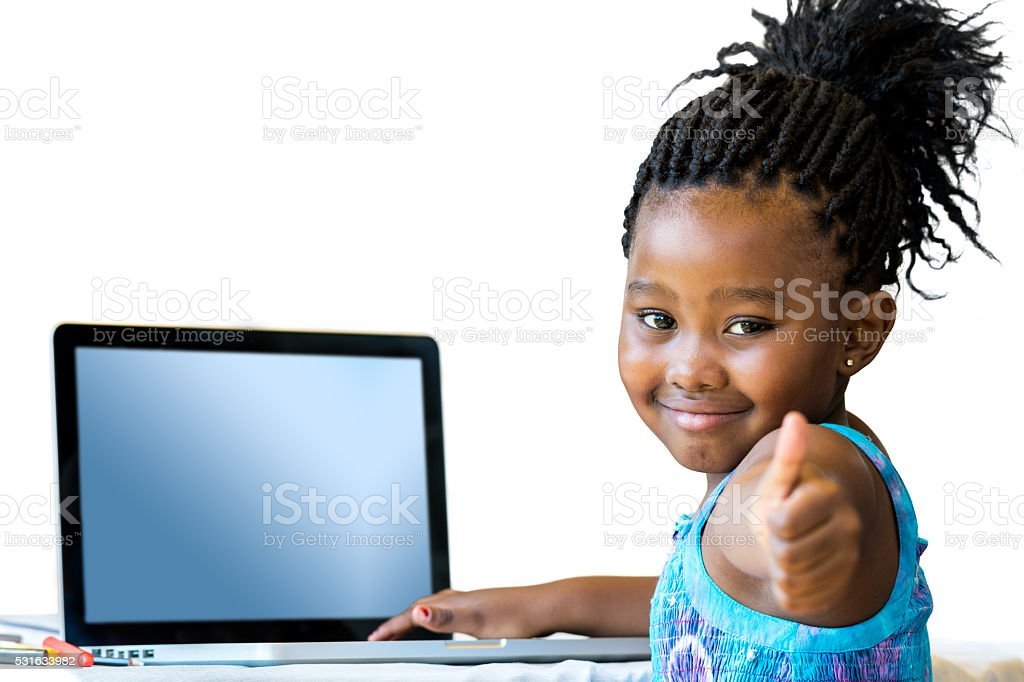 Little african girl doing thumbs up at desk. stock photo
