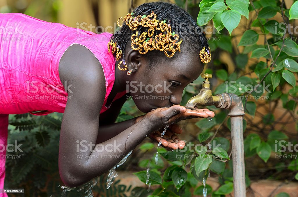 Little African Girl Drinking Hygienic Water from a Tap stock photo
