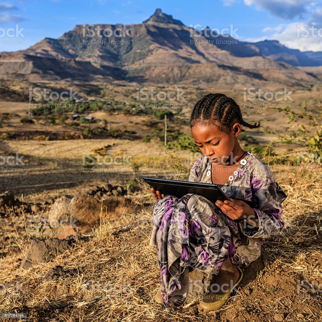 Little African girl is using digital tablet, East Africa stock photo
