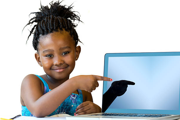 Little african girl pointing at blank laptop screen. stock photo
