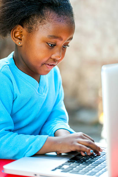 Little african girl typing on laptop. stock photo