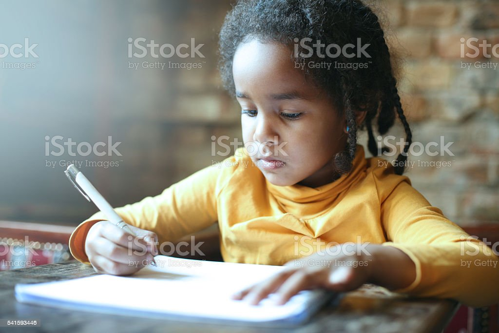 Little African girl writing. stock photo