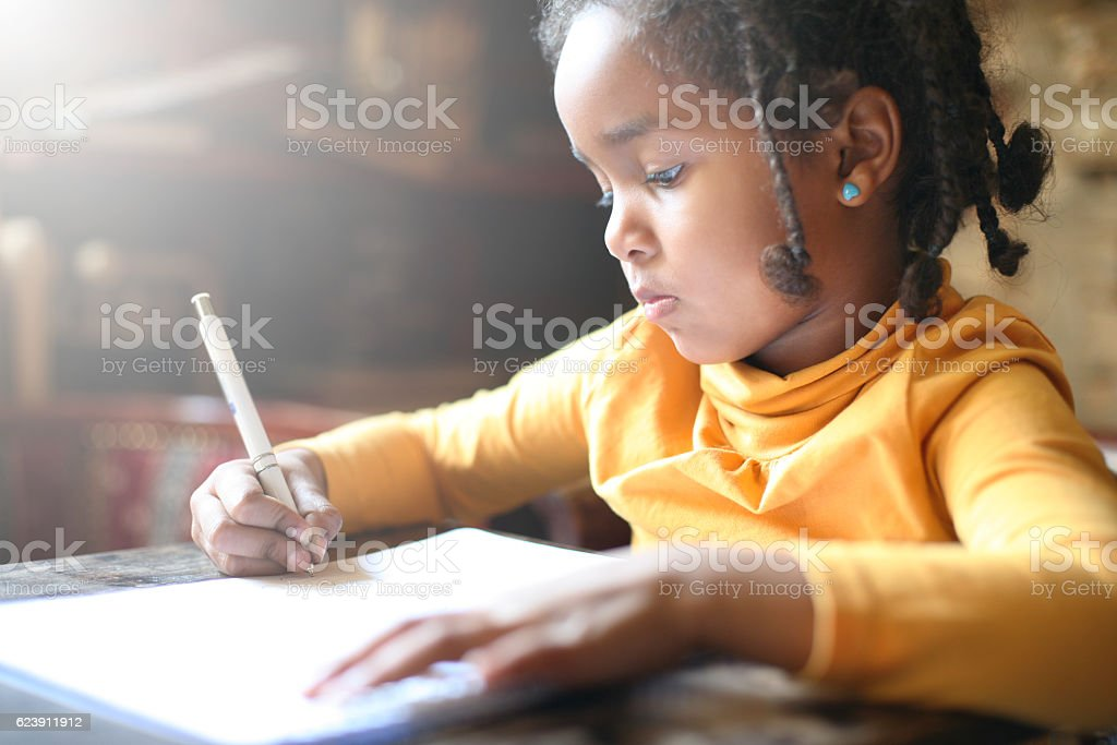 Little African girl writing. - foto de acervo