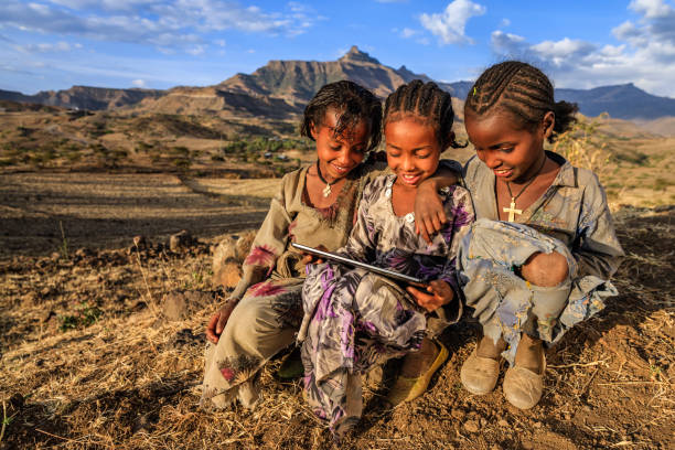 Little African girls using digital tablet, East Africa Little African girls using digital tablet in the village near to Lalibela town, northern Ethiopia, Africa. east africa stock pictures, royalty-free photos & images
