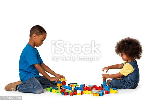 470874196istockphoto Little african kids playing with lots of colorful plastic blocks indoor. Isolated 1074272678