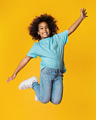 Little african-american girl jumping over yellow studio background