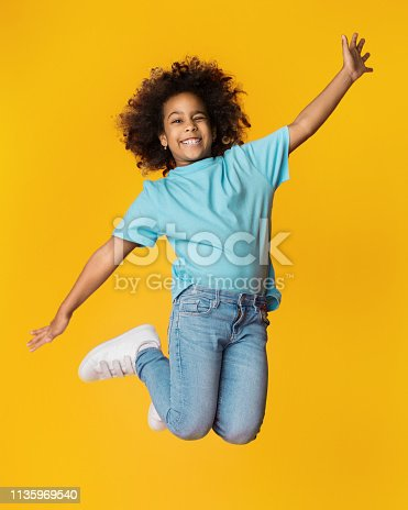 istock Little african-american girl jumping over studio background 1135969540