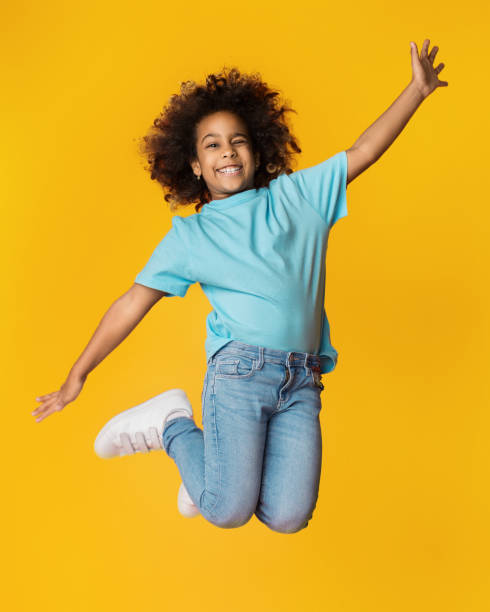 Little african-american girl jumping over studio background Little african-american girl jumping over yellow studio background mid air stock pictures, royalty-free photos & images