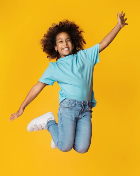 pequeña chica afroamericana saltando sobre fondo de estudio - saltar actividad física fotografías e imágenes de stock