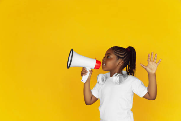 Little african-american girl's portrait isolated on yellow studio background stock photo