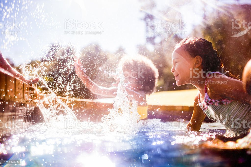 Little Afro girl and friends splashing in a pool together stock photo
