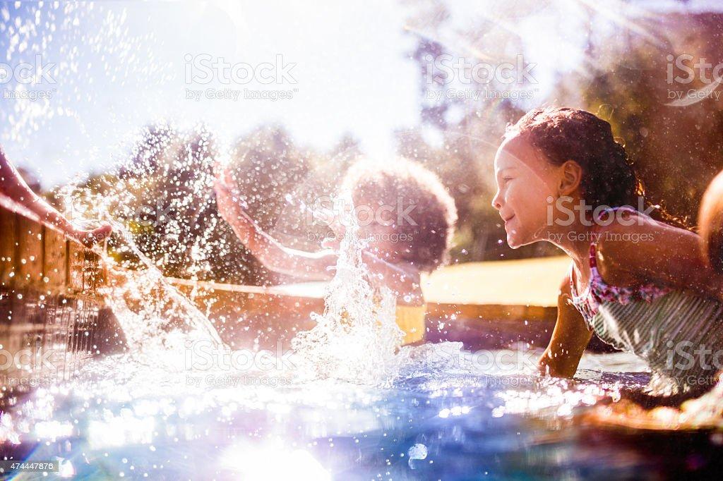 Piccola ragazza Afro e amici fare un tuffo in piscina insieme - foto stock