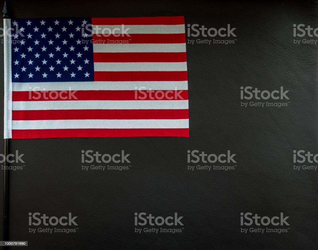 kleine amerikanische Flagge auf dunklem Lederoberfläche mit Platz für text – Foto