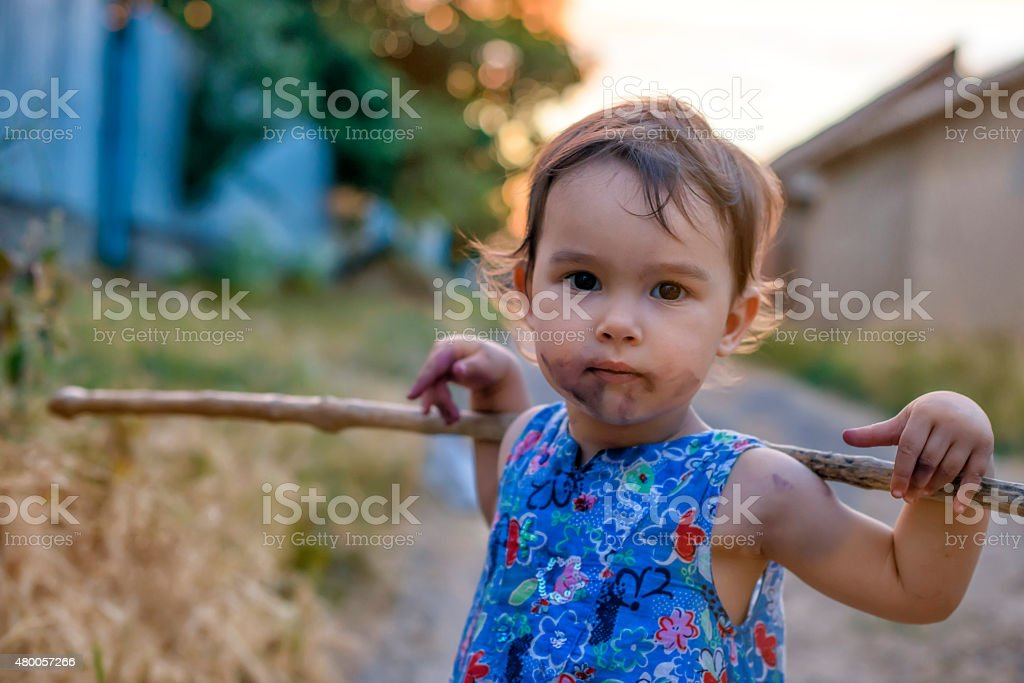 Little and dirty girl with her stick stock photo