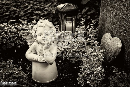 istock Little angel figurine and heart on the grave 986173246