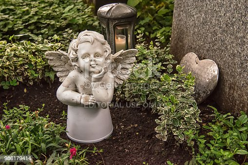 istock Little angel figurine and heart on the grave 986179414