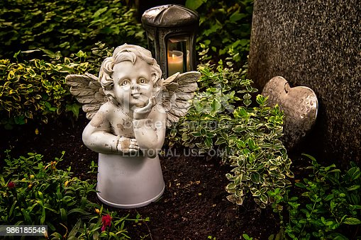 istock Little angel figurine and heart on the grave 986185548