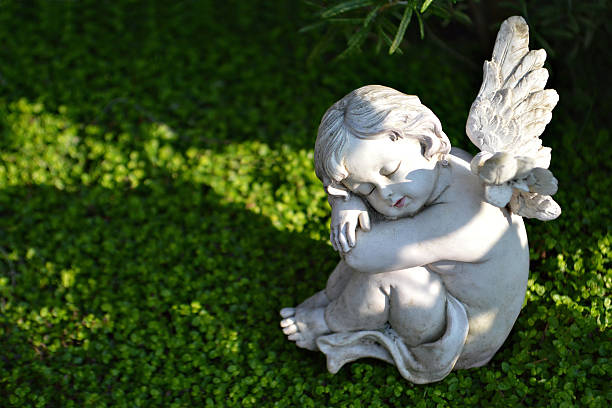 Little angel figurine on the grave stock photo
