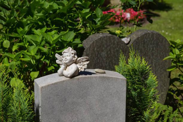 Kleiner Engel mit Flügeln liegt auf einem Marmorgrabstein – Foto