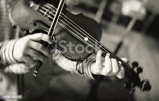 A little girl is practicing on her violin