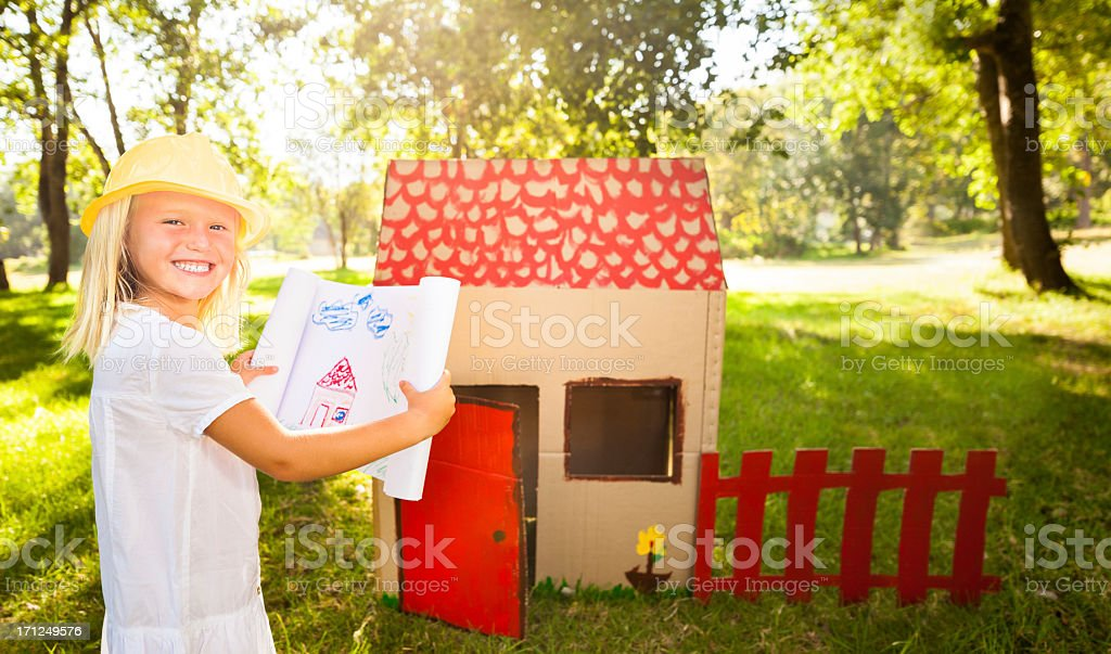 Little architect in front of playhouse stock photo