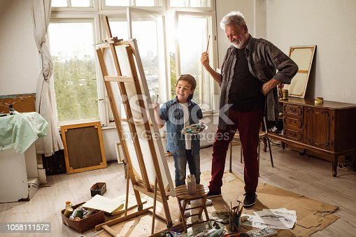 istock Little artist and grandpa 1058111572