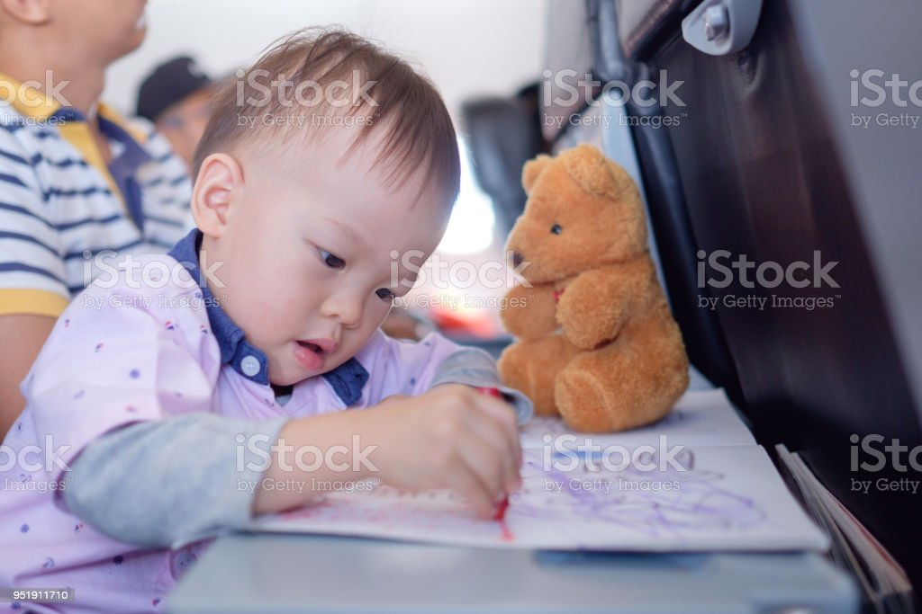 Little Asian 1 Year Old Toddler Boy Coloring In Book With Crayons During Flight On