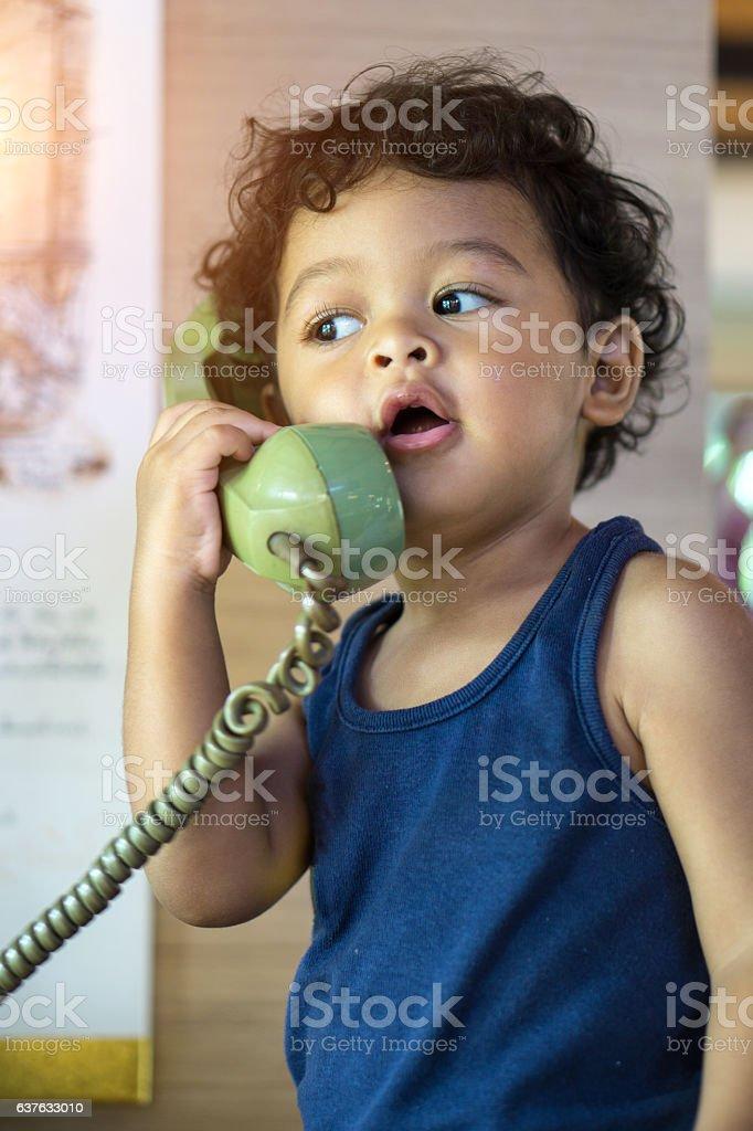 Little asian baby boy talking on a retro telephone. stock photo