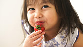 Little Asian baby girl is eating strawberry at her room