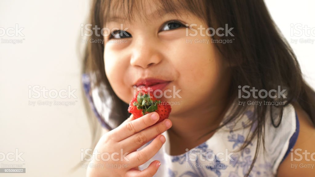 Little Asian baby girl is eating strawberry at her room stock photo