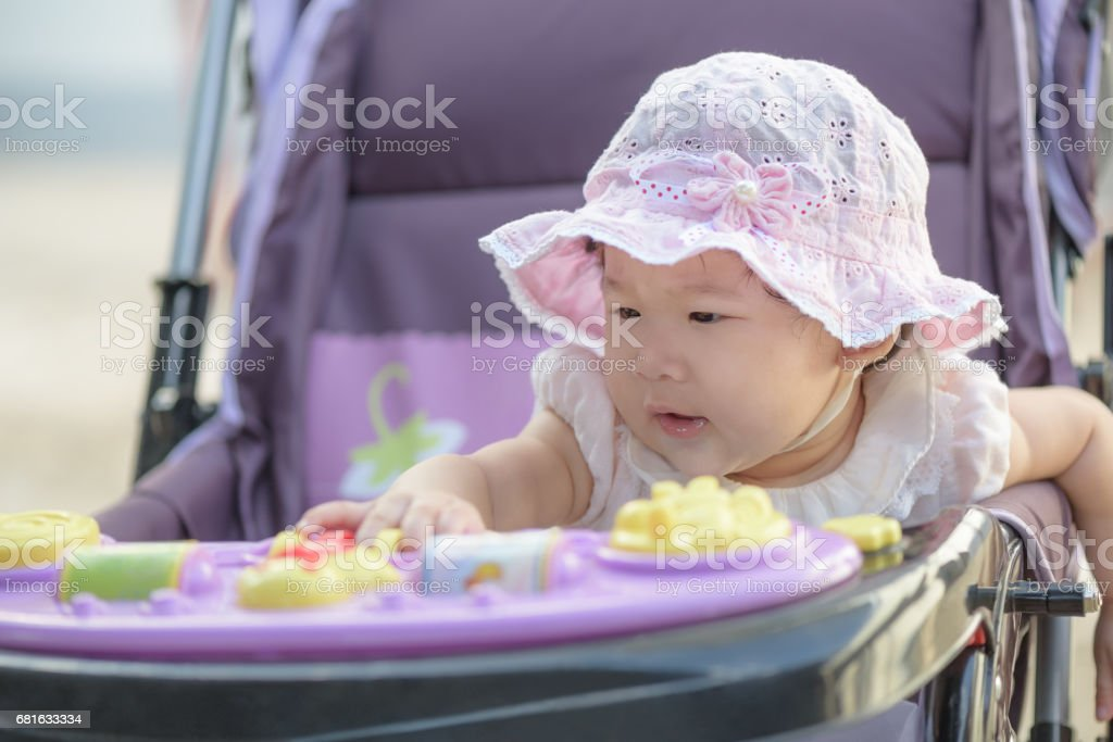 Little asian baby girl sitting and playing in stroller on a walk. stock photo