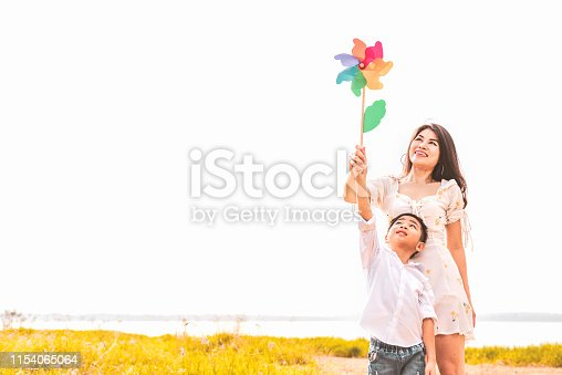 istock Little Asian boy and his mom playing colorful rainbow turbine in meadow. Mother and son playing together. Celebrating in Mother day and appreciating concept. Summer people and lifestyle theme. 1154065064