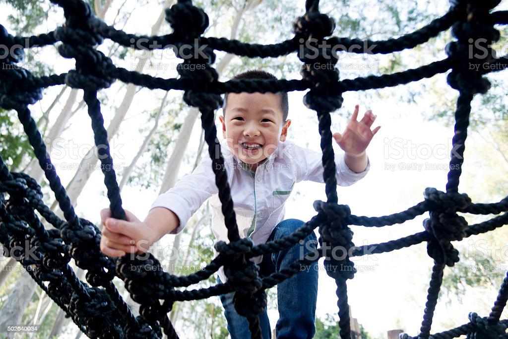 Little asian boy climbing rope frame stock photo