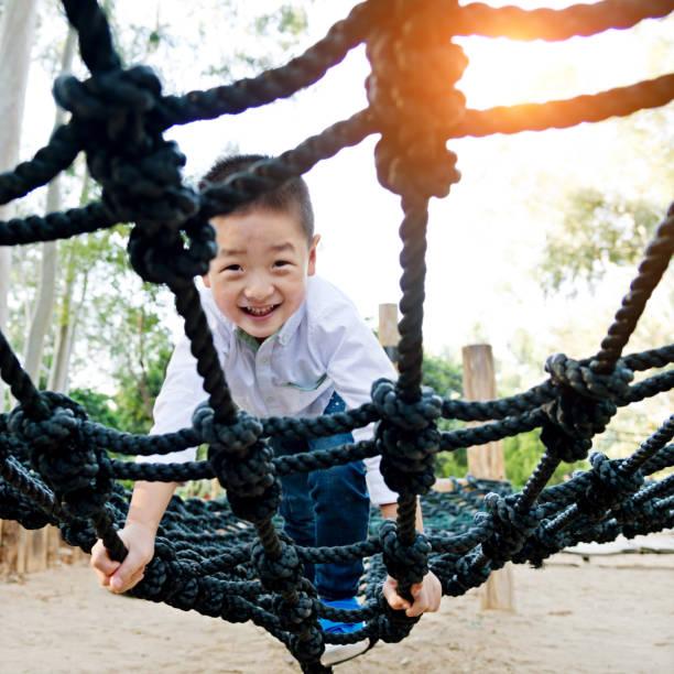 小さなアジアの少年クライミングロープフレーム - 小学校低学年 ストックフォトと画像