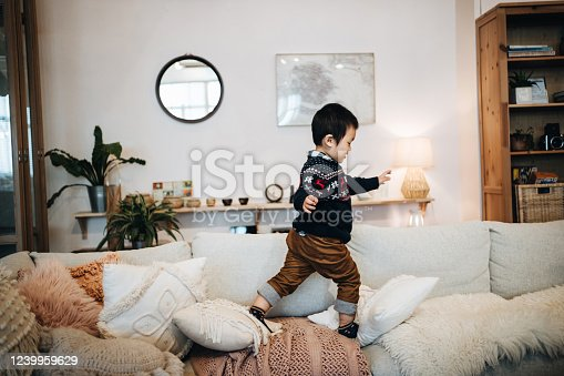 Little Asian boy having fun running and jumping on the sofa at home