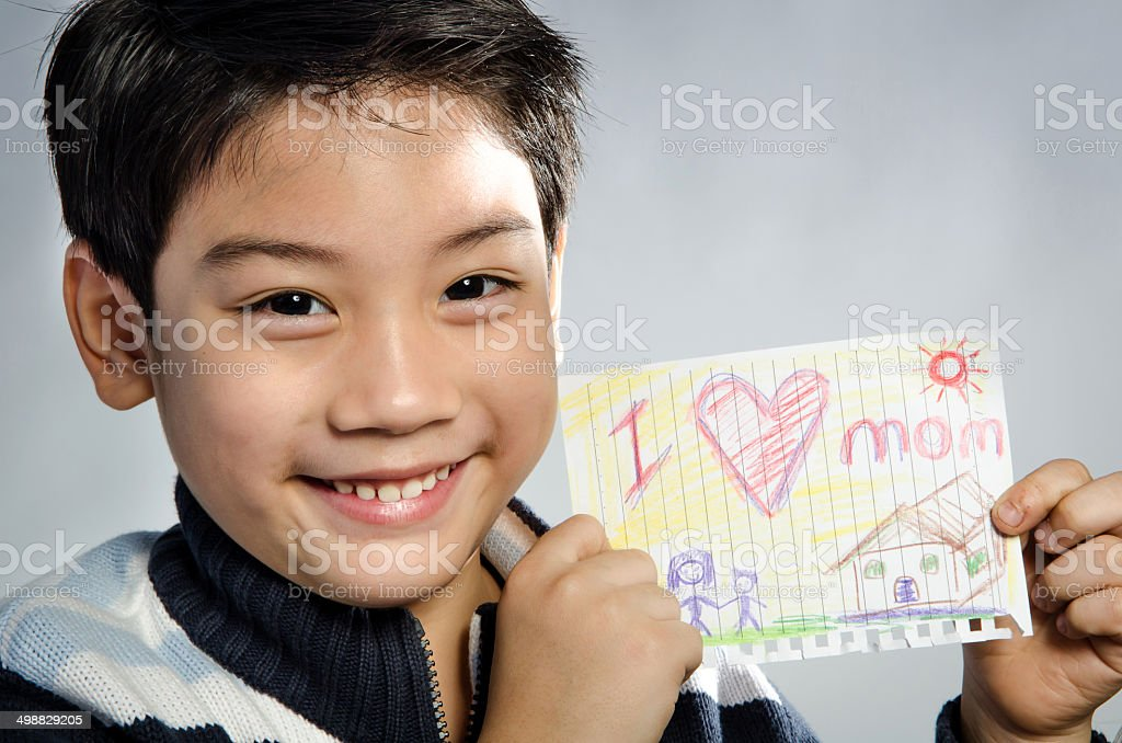 Little asian boy holding picture stock photo