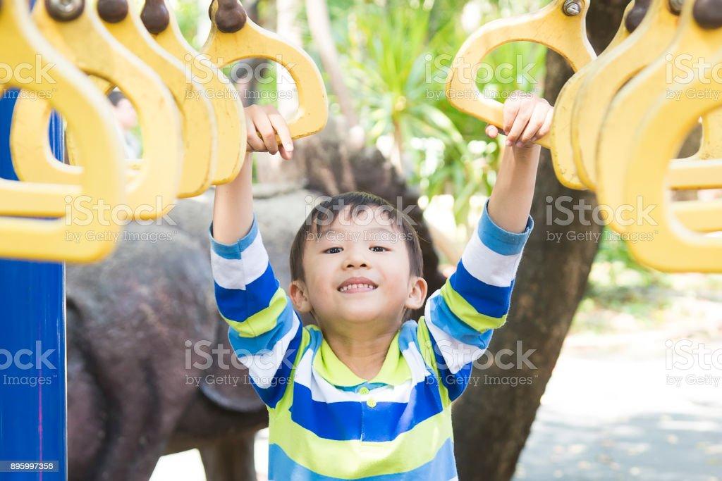 Little Monkey Klettergerüst : Kleine asiatische junge spielt auf klettergerüst spielplatz