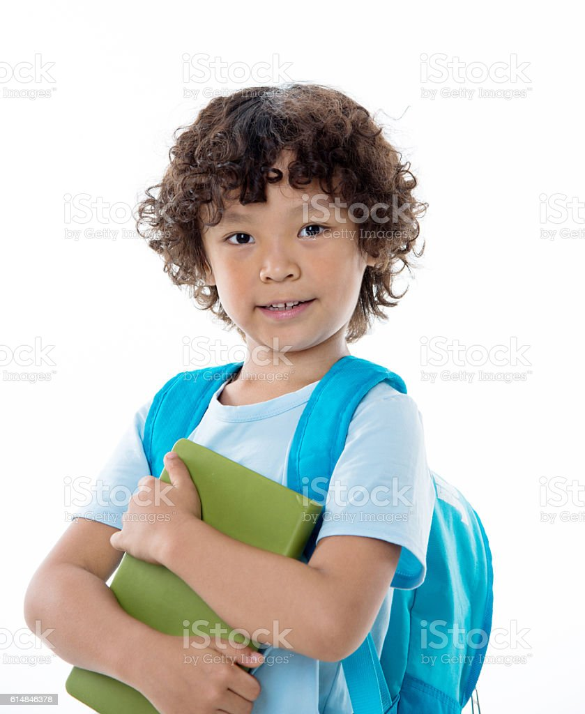 Little asian boy with a book against white background stock photo