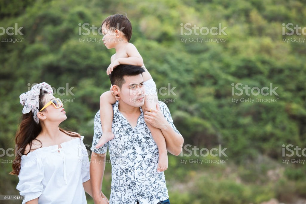 Little asian child boy riding on father's shoulder with mother and father holding hand and walking on the beach together stock photo