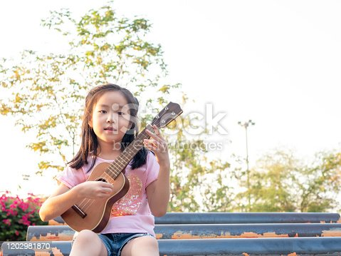 Little asian child girl play the ukulele, in the garden on the Steel pipe