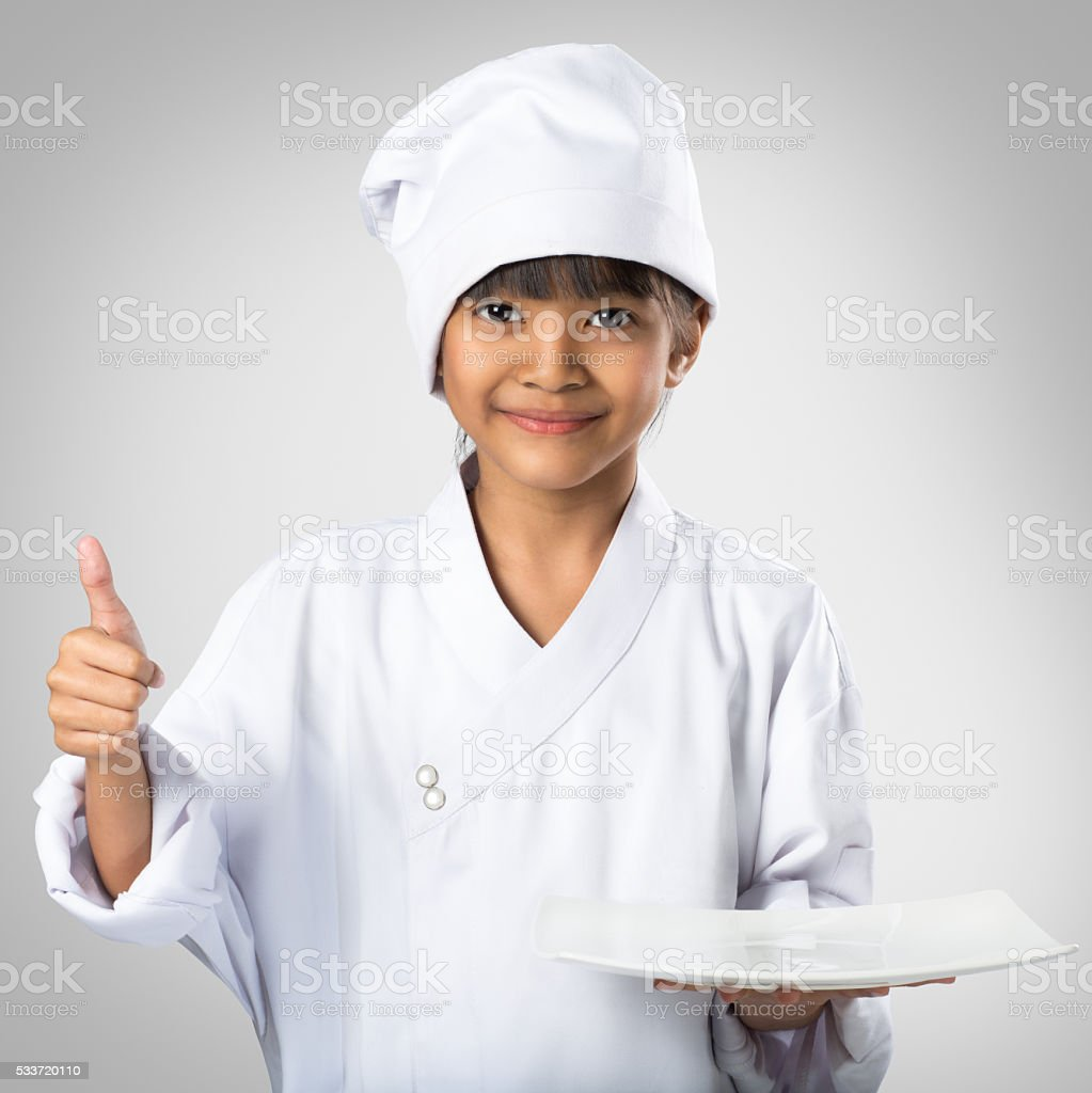 Little asian girl chef showing the empty white plate stock photo