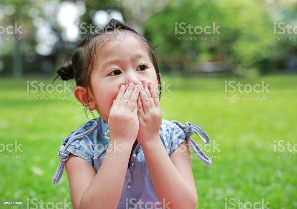 Little asian girl covering her mouth and nose with her hands. royalty-free stock photo