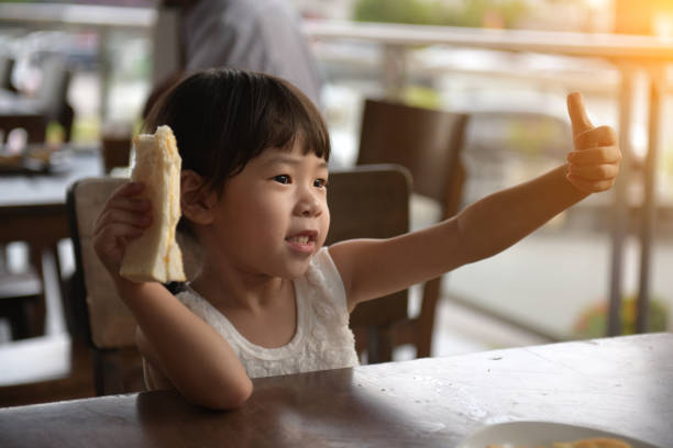 little asian girl drinking at cafe stock photo