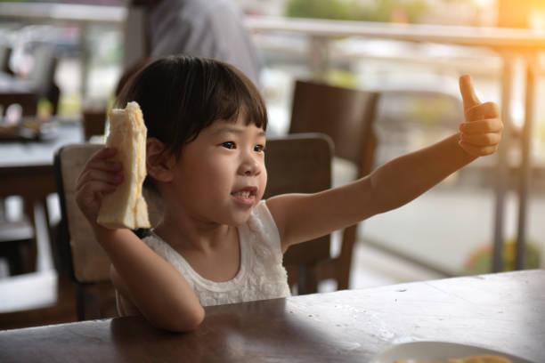 menina asiática pequena que bebe no café - foto de acervo