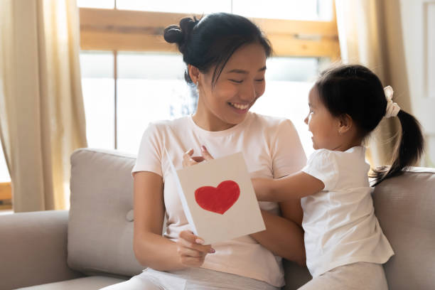 Little Asian girl greeting mom presenting postcard Loving little Asian girl hug congratulate overjoyed ethnic mother with birthday or anniversary at home, cute biracial child greeting Vietnamese mom present handmade postcard, celebration concept birthday wishes for daughter stock pictures, royalty-free photos & images