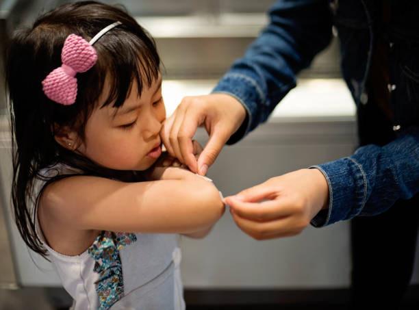 Little asian girl having a plaster put on by big sister. stock photo
