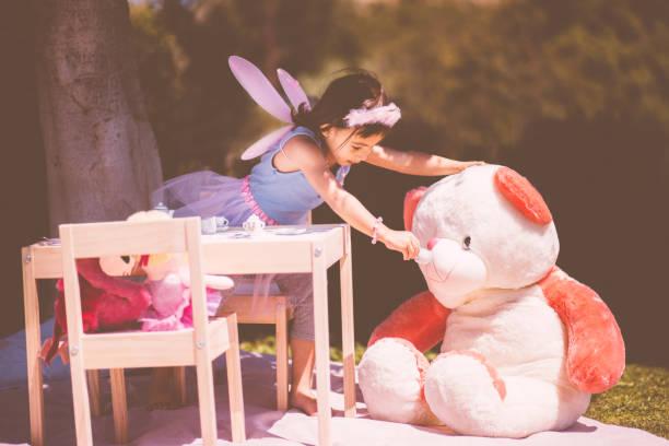 kleine asiatin mit einer tee-party mit teddybär - sommerfest kindergarten stock-fotos und bilder