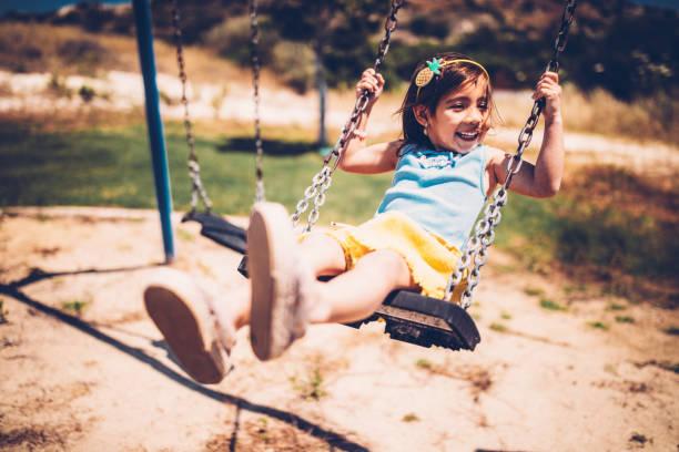 Little Asian girl having fun on the swings stock photo