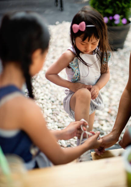 Little asian girl having her shoe tied by big sister. stock photo